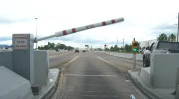 A toll booth arm swings upward