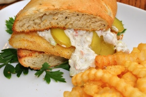A breaded fish sandwich on a plate with French fries