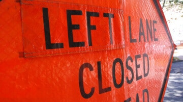 "A close-up photo of a ""left land closed ahead"" sign"