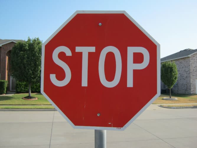 A stop sign set against a suburban neighborhood background and a clear blue sky