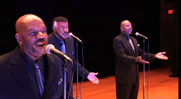 The gospel group Voices For Christ performs on a stage in a scene from a music video