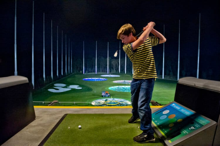 A visitor to the Alpharetta, Georgia Topgolf takes swings at the driving range