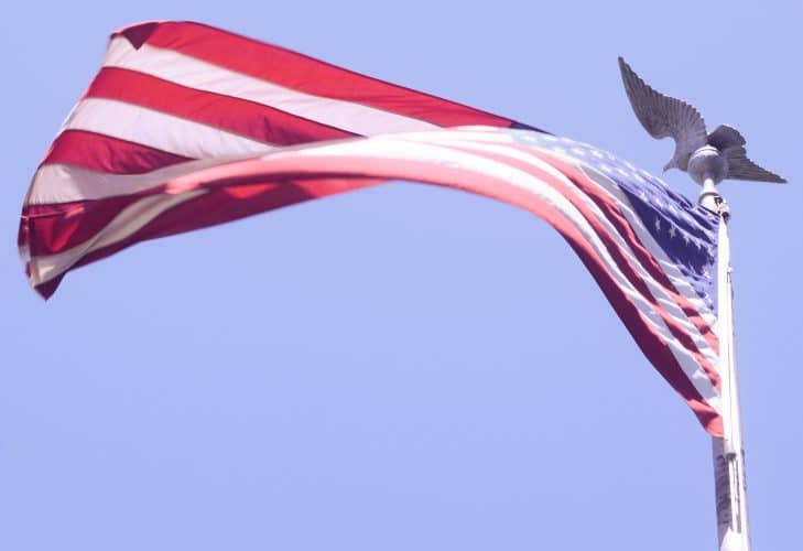 A U.S. flag pictured against a blue sky