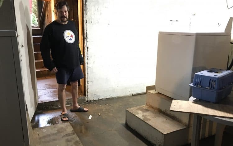 Todd Bradley, of Baldwin Street, explains his flood-conscious washer-dryer set-up.