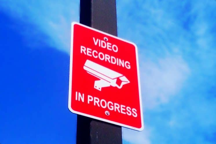 """A parking lot sign that reads: """"Video Recording in Progress"""""""