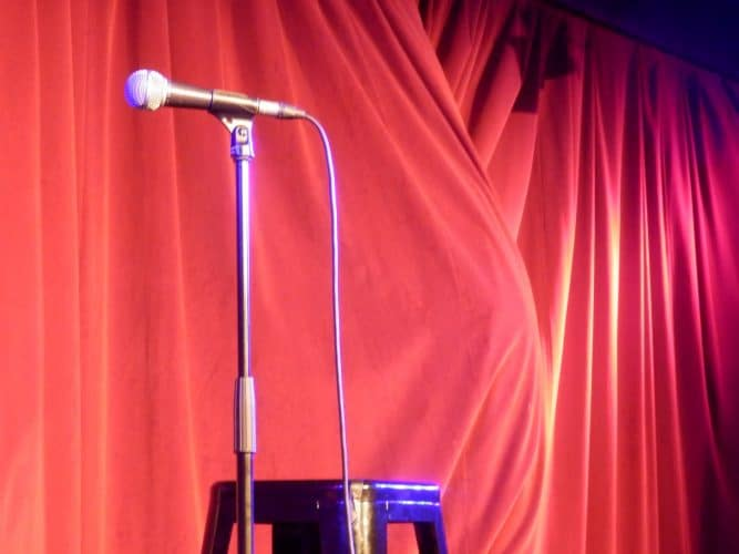 A microphone in front of a stage curtain.