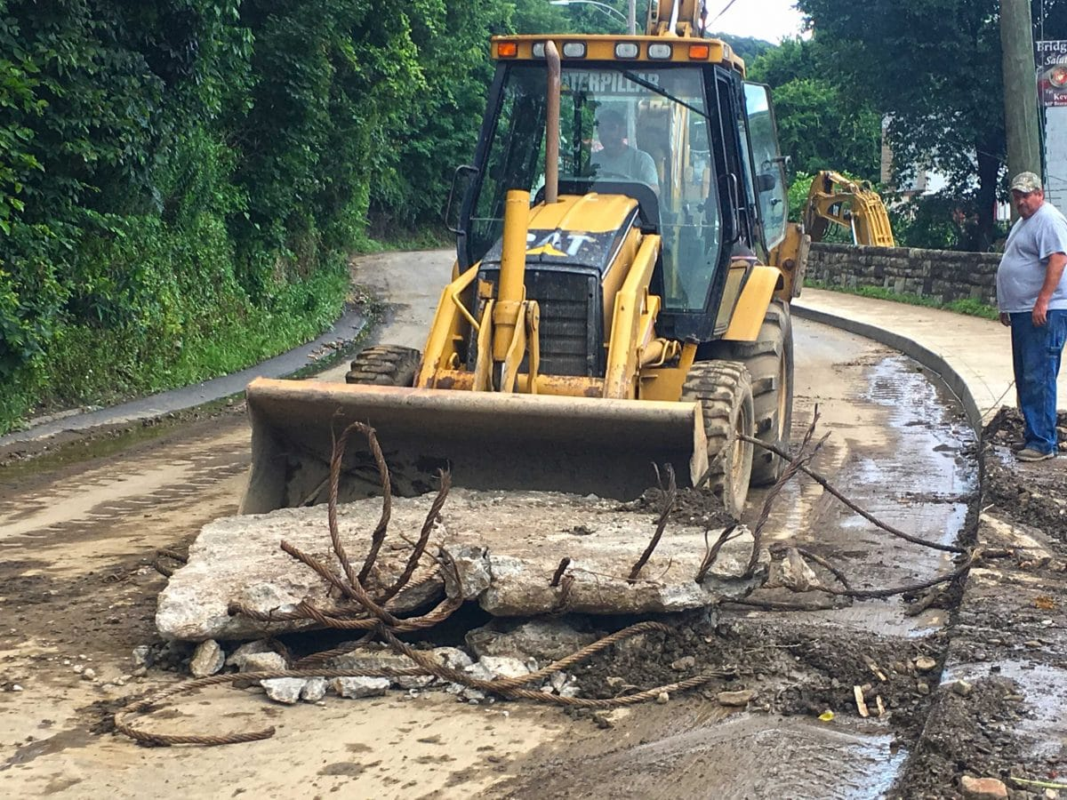 A bulldozer moves a piece of concrete and rebar that washed into Bridgeville during the June 20 flood