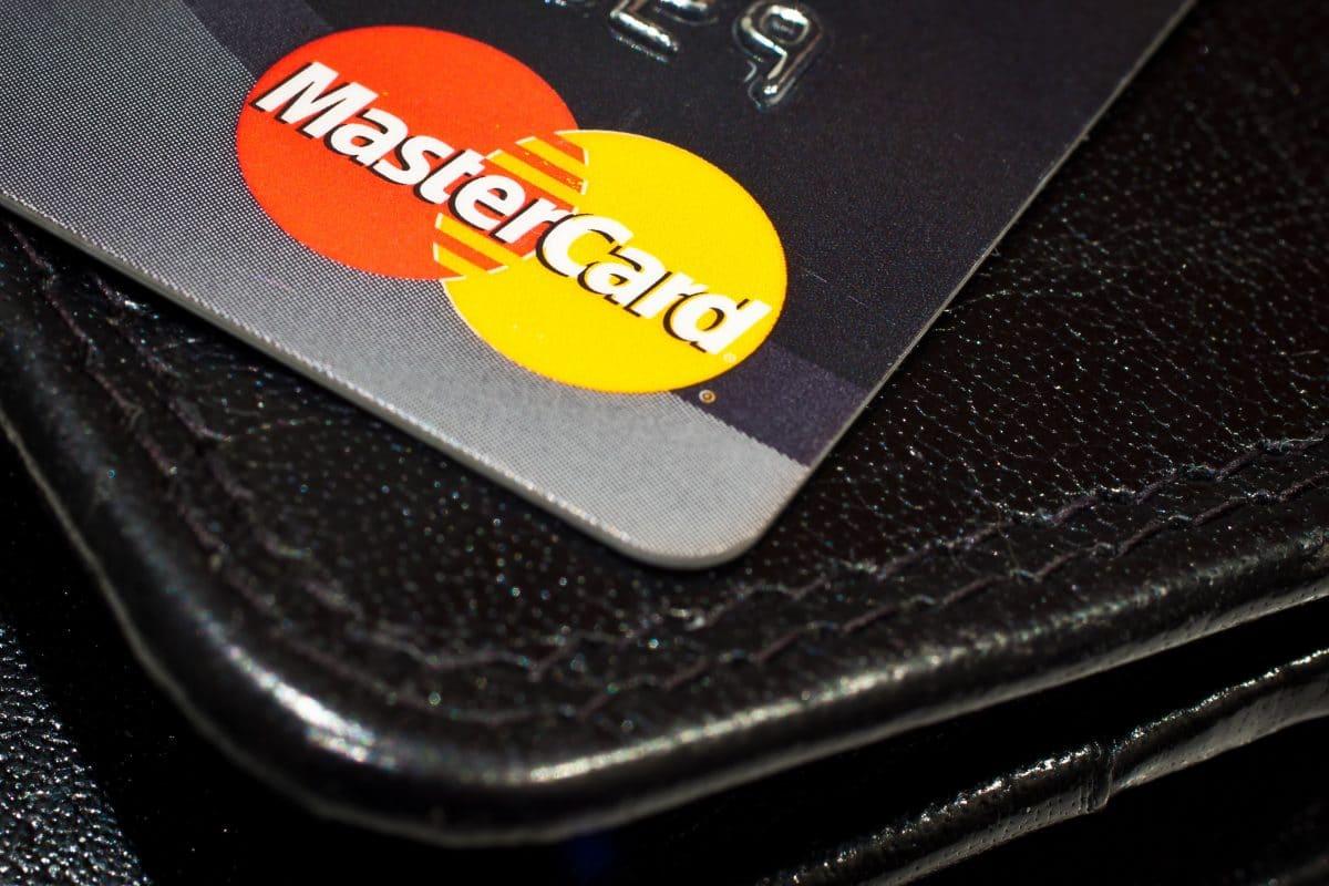 A MasterCard credit card sits atop a black wallet.
