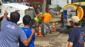 Workers clear debris from a sewer on Saturday, June 23, 2018.
