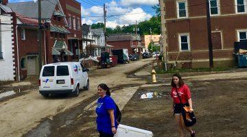 Two woman walk down Baldwin Street after the June 2018 flood.