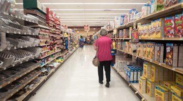 A woman walks down an aisle at Giant Eagle