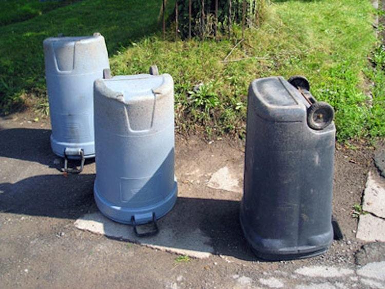 Three empty trash cans placed upside down on sidewalk