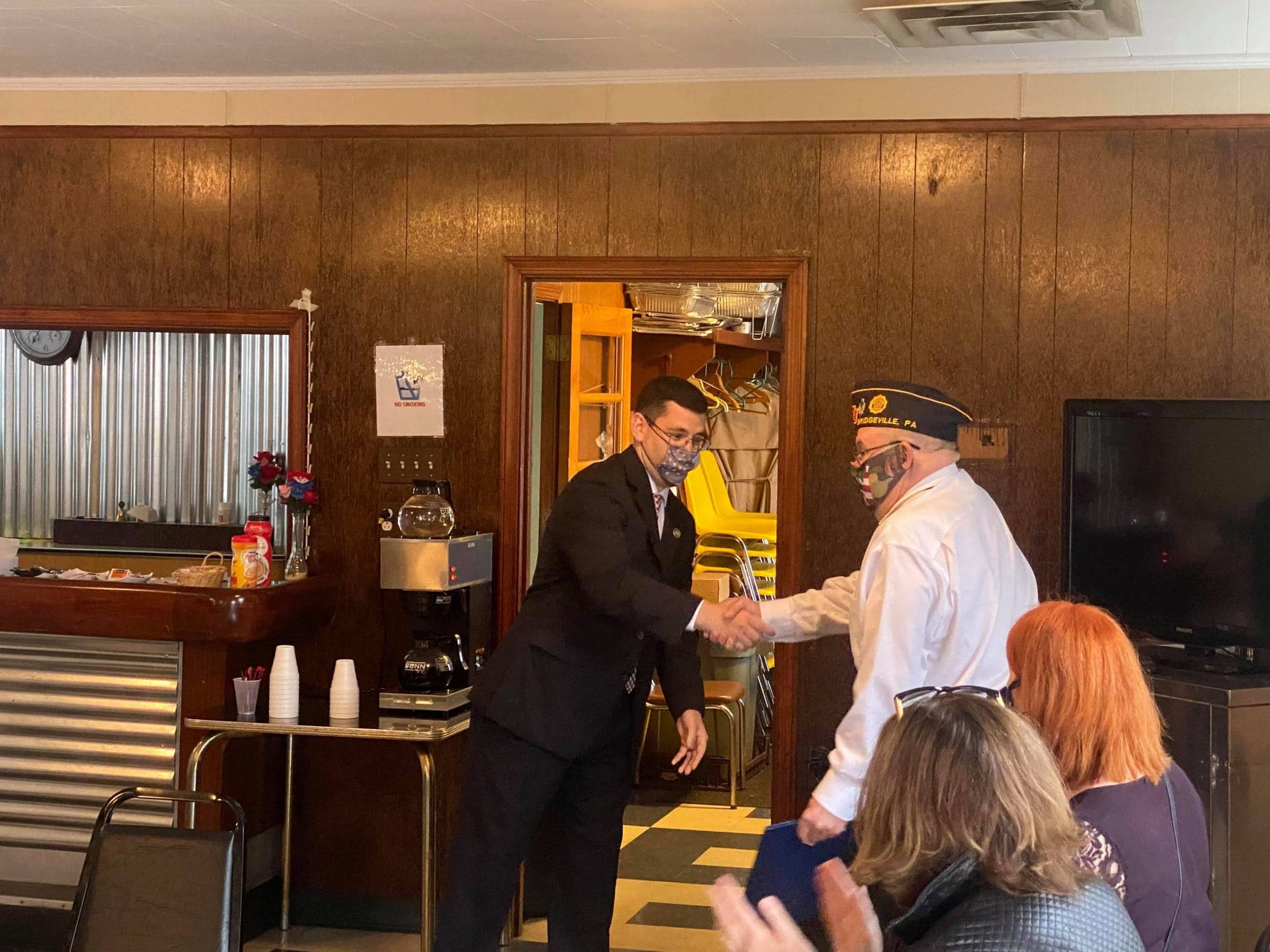 State Rep. Jason Ortitay shakes hands with an officer of American Legion Post 54