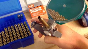 A home reloader uses a hand-priming tool while assembling cartridges