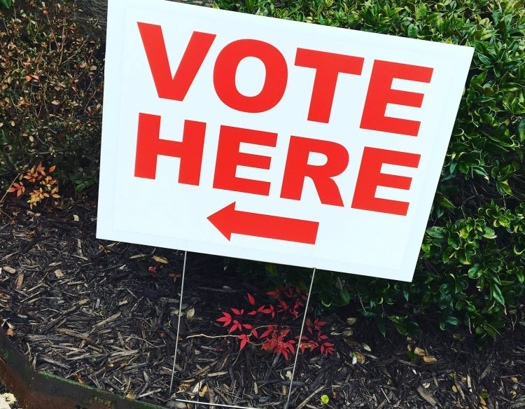 """A """"Vote Here"""" sign outside of a polling location."""