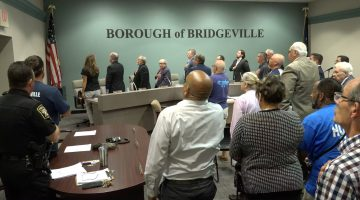 Borough council meeting attendees stand for the pledge of allegiance at the September 2021 council meeting.